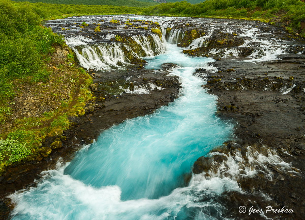 blue glacial water and waterfall south iceland jens